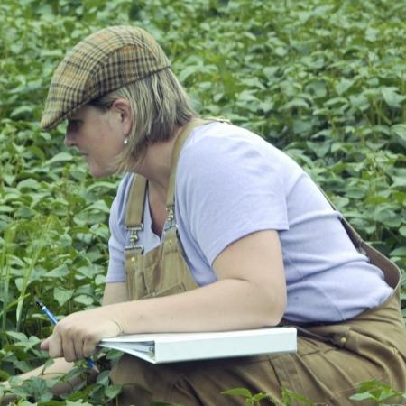 A woman in a field with a notebook